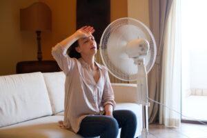 woman-sitting-in-front-of-floor-fan-looking-hot