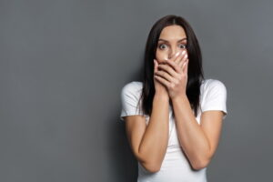 shocked-woman-covering-mouth-with-both-hands