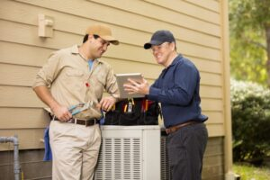 two-technicians-checking-on-outside-ac-unit